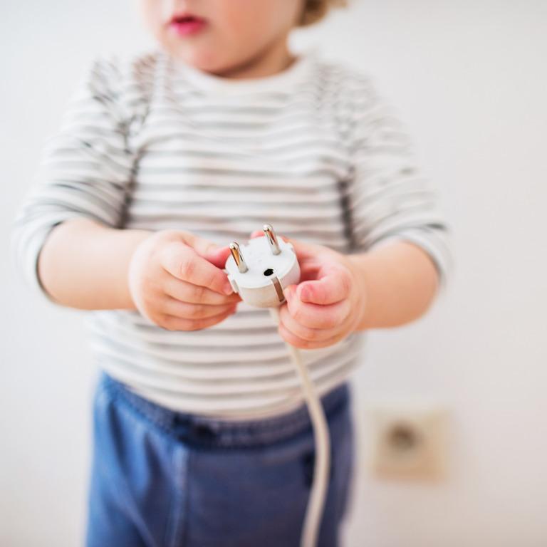 Kleinkind hält den Stecker eines Elektrogerätes in der Hand