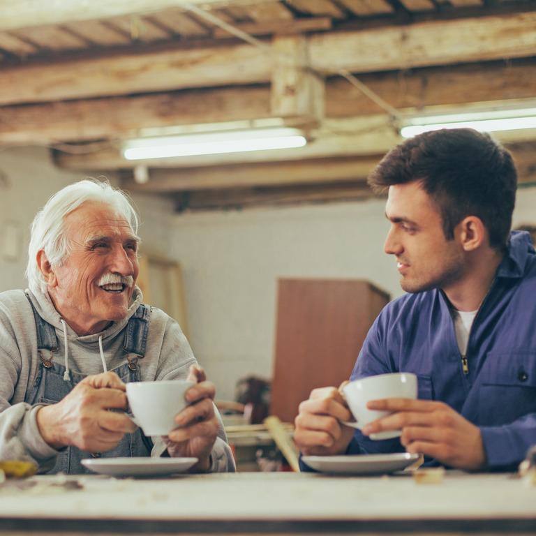 Älterer Mann sitzt mit einem jungen Mann zur Kaffeepause in der Werkstatt an einem Tisch