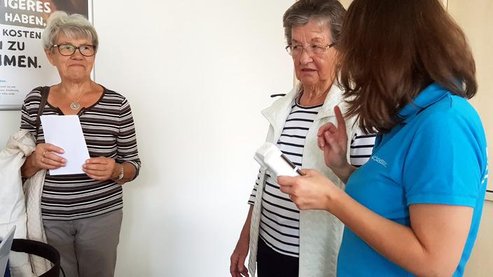 IKK-Mitarbeiterin erklärt Besuchern die Körperfettanalyse