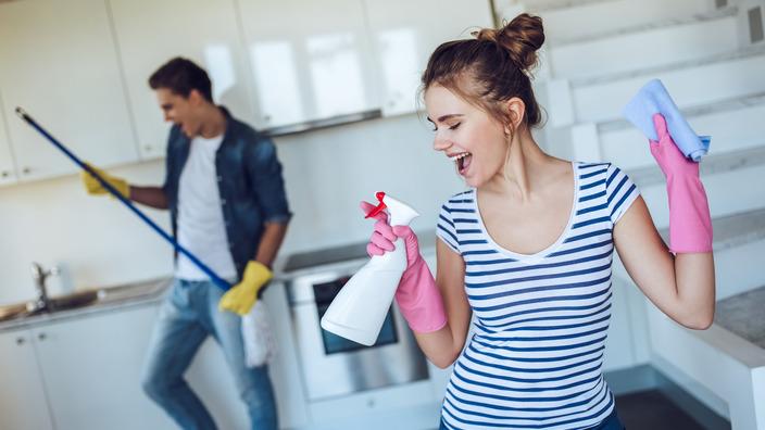 junges Paar tanzt beim Putzen durch die Wohnung
