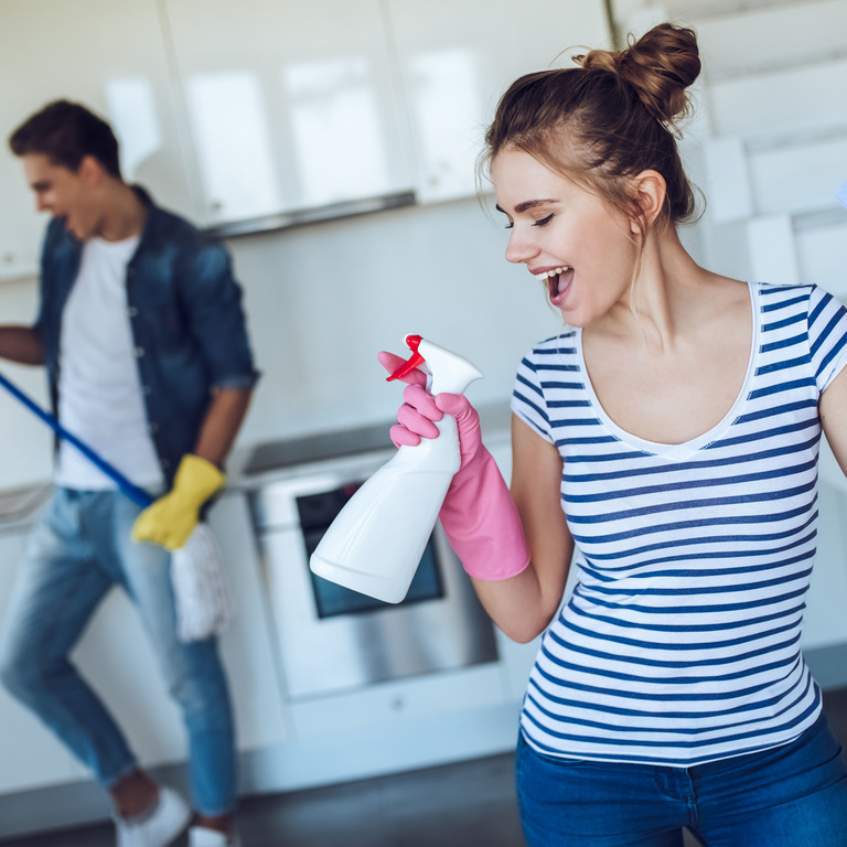 junger Mann mit Wischmopp und junge Frau mit Sprühflasche albern herum beim Kücheputzen