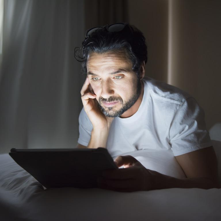 Mann sitzt allein im Dunkeln und schaut auf das Display seines Tablets