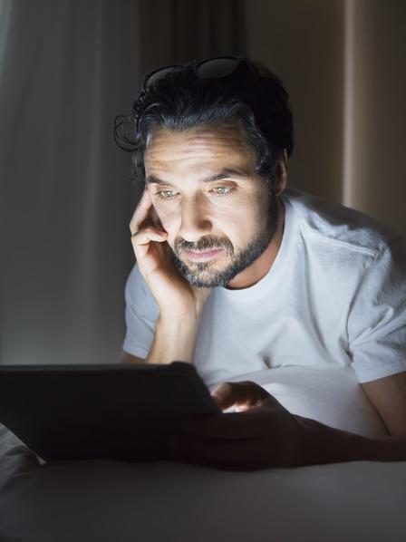 Mann liegt im Dunkeln auf dem Bett und liest etwas auf seinem Tablet