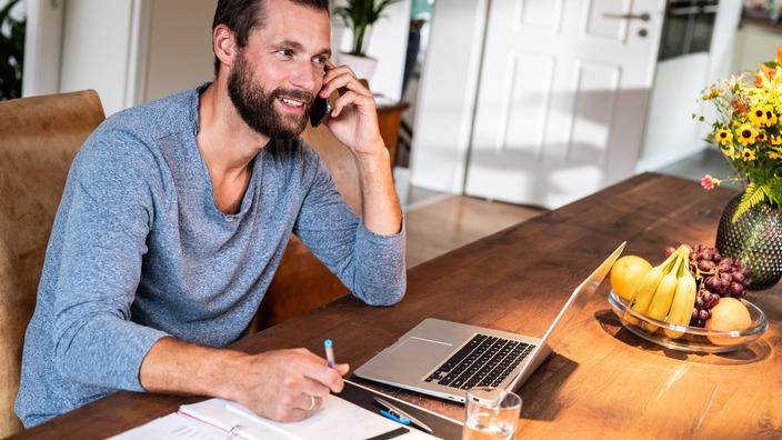 Mann telefoniert zuhause am Esstisch und prüft seine Unterlagen