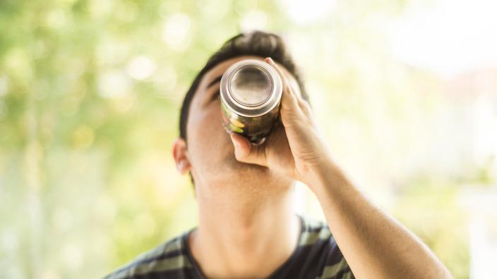 Teenager trinkt einen Energy-Drink aus der Dose