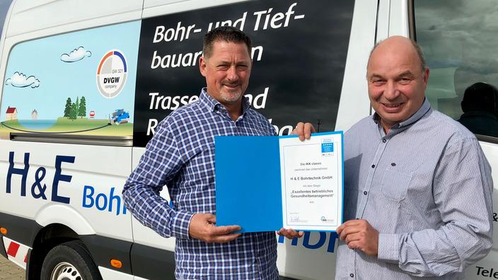 Urkundenübergabe vor dem Firmenwagen der H & E Bohrtechnik