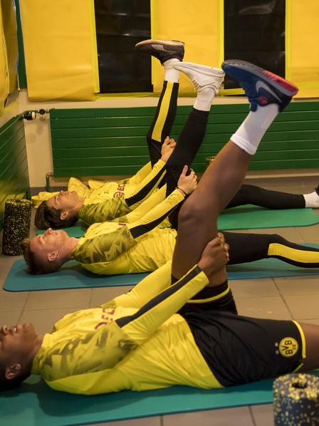 BVB-Spieler liegen auf Matten und dehnen ihre Muskeln