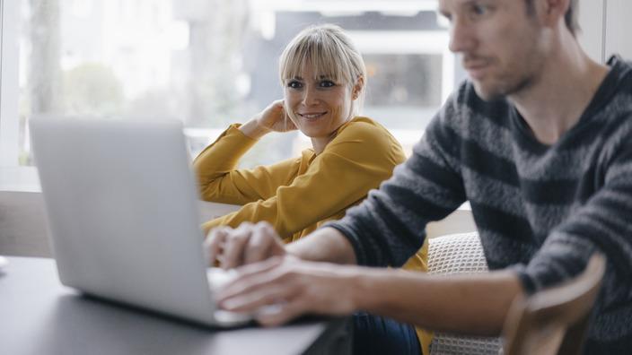 Mann sitzt am Laptop, lächelndes Kind im Hintergrund.
