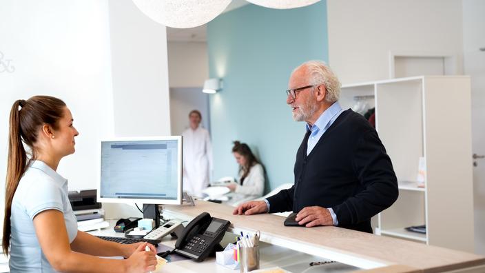 älterer Patient redet mit einer Sprechstundenhilfe