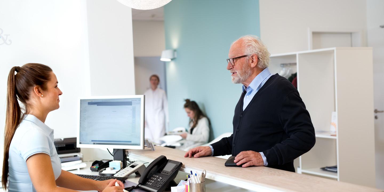 Alter Mann steht am Empfang in Arztpraxis und spricht mit einer Arzthelferin
