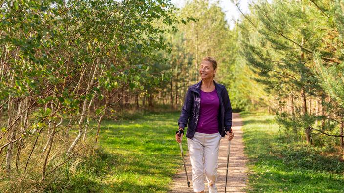 Frau beim Nordic Walking durch den Wald