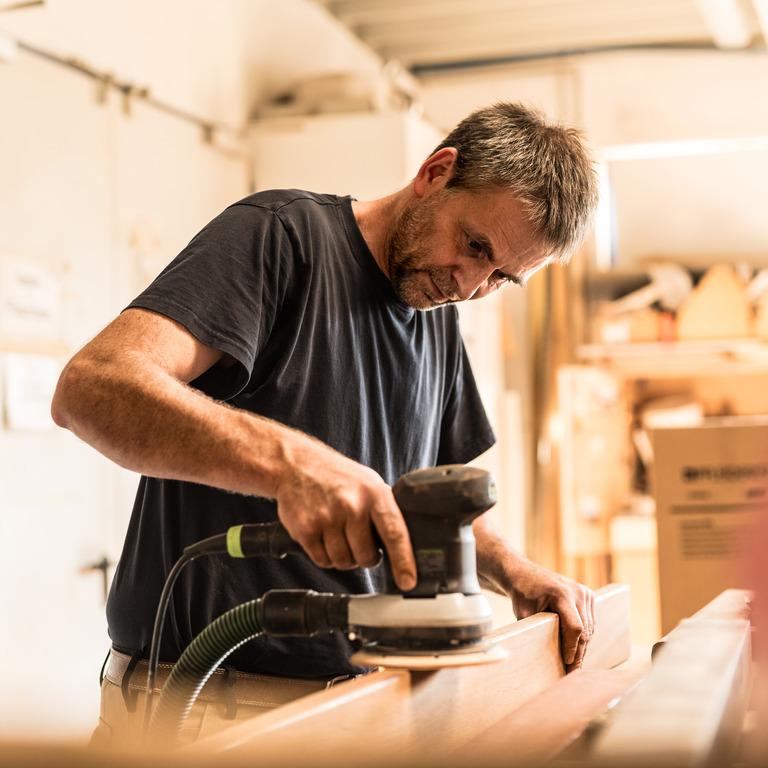 Ein Tischler oder Schreiner mit einer Schleifmaschine am Werk.
