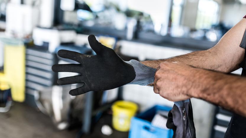 Mann streift sich einen Arbeitshandschuh über
