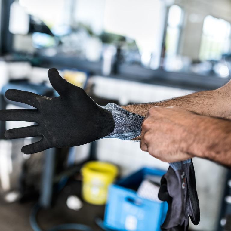 Arme eines Mannes, der sich in einer Werkhalle schwarze Handschuhe anzieht.