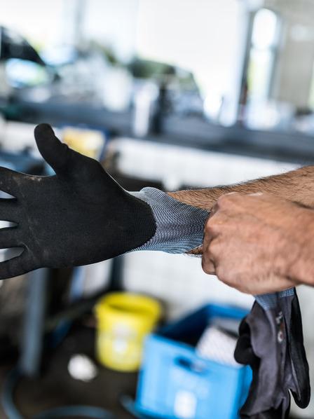 Handwerker zieht einen Arbeitshandschuh an