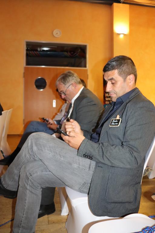 Teilnehmer sitzen auf den Stühlen und stimmen live mit ihren Smartphones ab