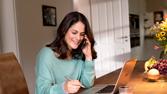 Frau telefoniert zuhause am Esstisch und prüft ihre Unterlagen