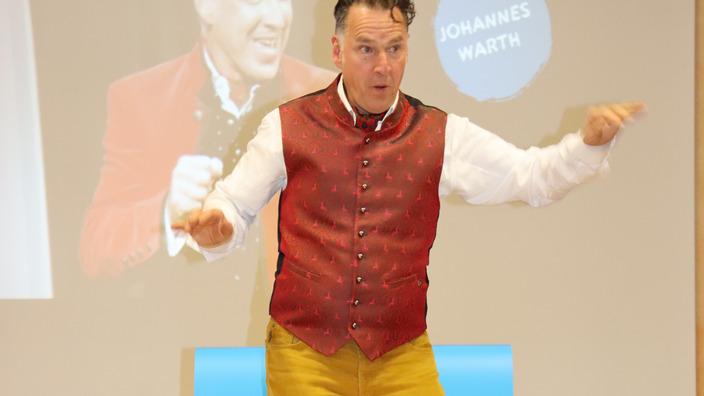 Coach Johannes Warth bei Balance-Übung auf der Bühne