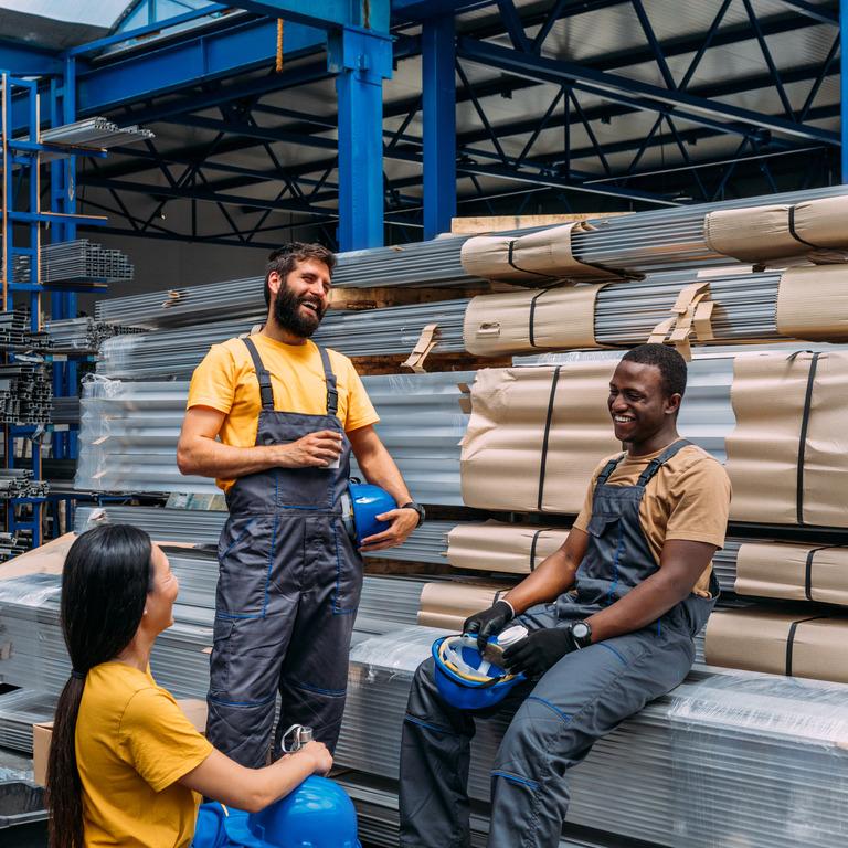 Mehrere Arbeiter stehen in Produktionshalle zusammen und lachen