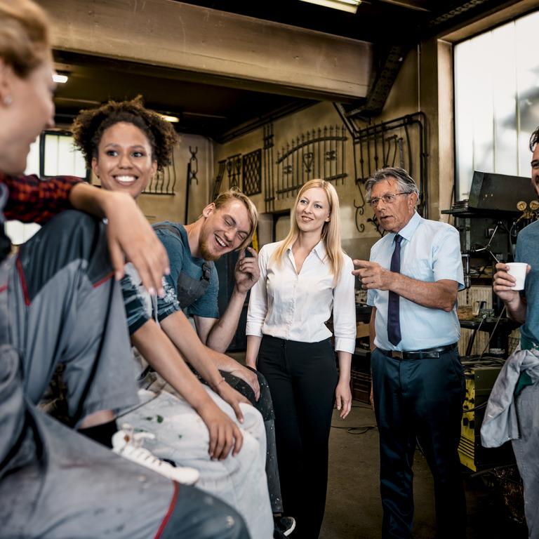 Chef steht mit mehreren Auszubildenden in der Runde zusammen in einer Werkstatt