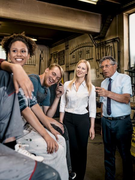 Kollegen aus Büro und Werkstatt stehen während einer Kaffeepause beieinander