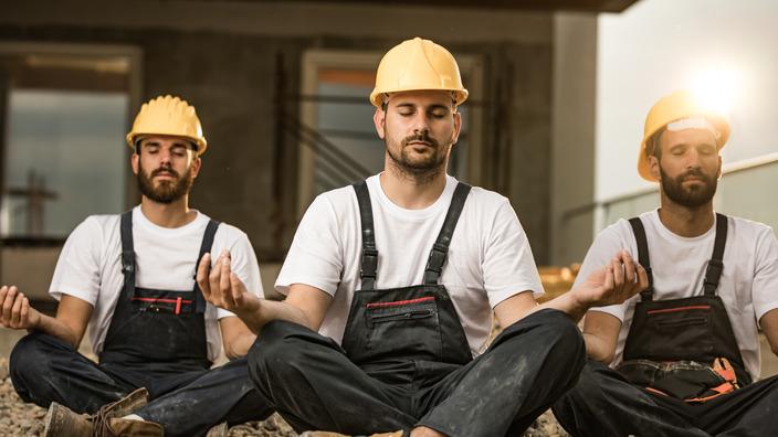 drei Bauarbeiter mit Latzhose und gelbem Helm sitzen im Lotussitz auf dem Boden einer Baustelle und meditieren