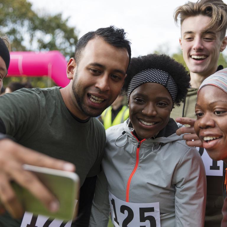 Menschen unterschiedlichster Nationalität in Laufkleidung machen nach einem Laufwettbewerb ein Gruppen-Selfie