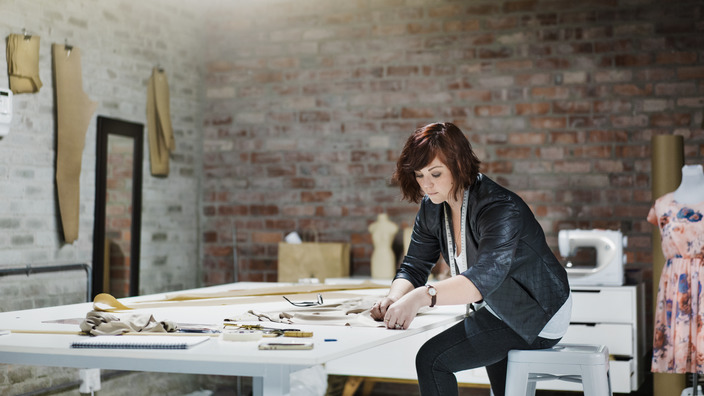 Junge Frau in Werkstatt beugt sich über Schnittunterlagen