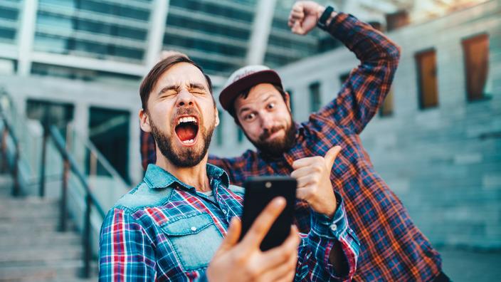 zwei junge Männer schauen auf ein Smartphone und jubeln