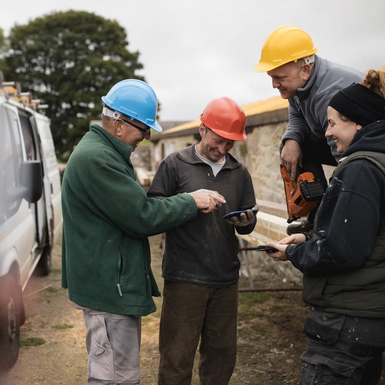 Handwerkerin und Handwerker stehen auf Baustelle neben Fahrzeug.