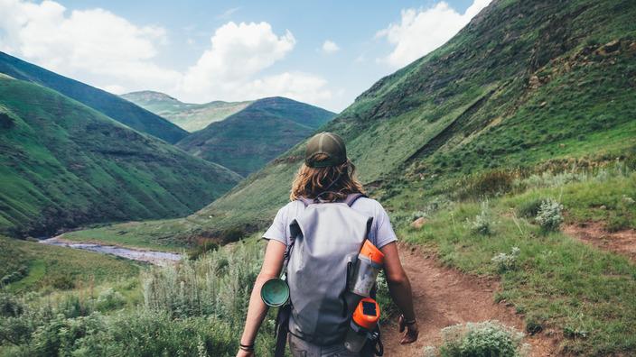 sportlicher junger Mann wandert mit dem Rucksack durch eine Berglandschaft