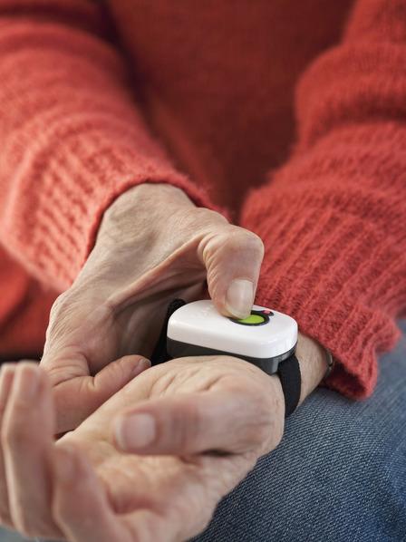 Ältere Person betätigt Alarmknopf am Handgelenk