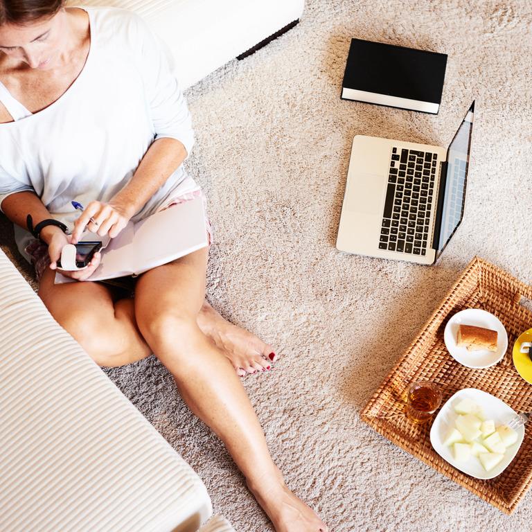 Frau sitzt auf dem Wohnzimmerboden