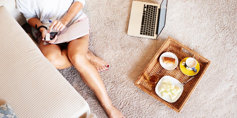 Frau sitzt auf dem Wohnzimmerboden und schont ihre Beine