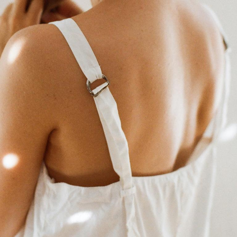 Rückenansicht einer jungen Frau mit Träger-Top