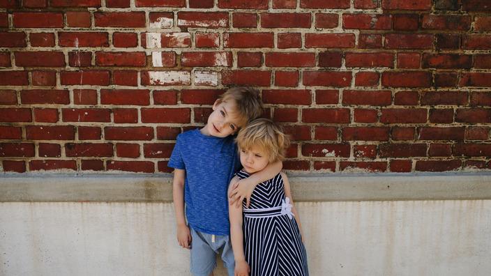 Junge in blauem T-Shirt hält seine kleine Schwester im Arm