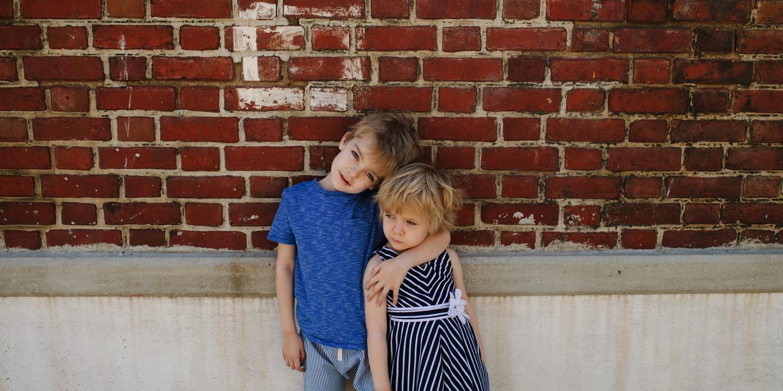 Junge hält seine kleine Schwester schützend im Arm