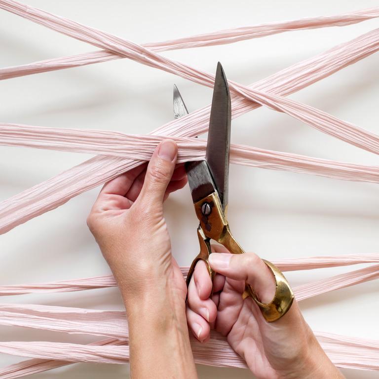 Schere schneidet rosa Bänder auseinander