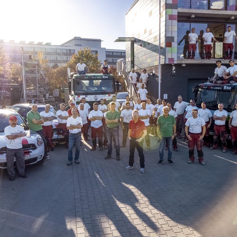 Gruppe von Mitarbeitern vor einem Firmengebäude