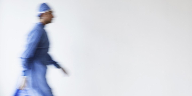 Arzt im OP-Outfit läuft vor weißer Wand