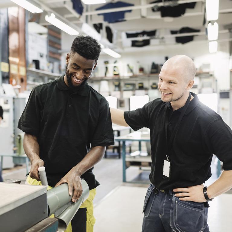 Arbeiter mit Migrationshintergrund unterhält sich mit einem Kollegen in der Produktionshalle