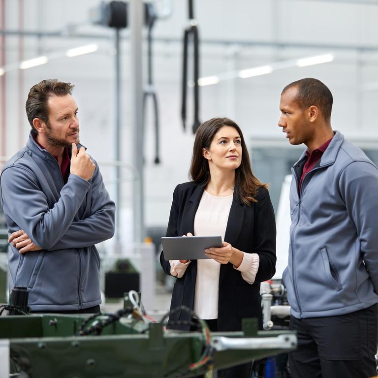 Mehrere Kollegen stehen zusammen in einer Produktionshalle