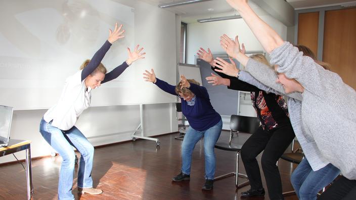 IKK-Präventionsexpertin zeigt Teilnehmern eine Rückenübung