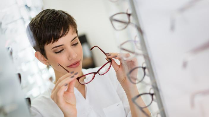 Junge Frau probiert Brille vor einem Spiegel im Brillengeschäft