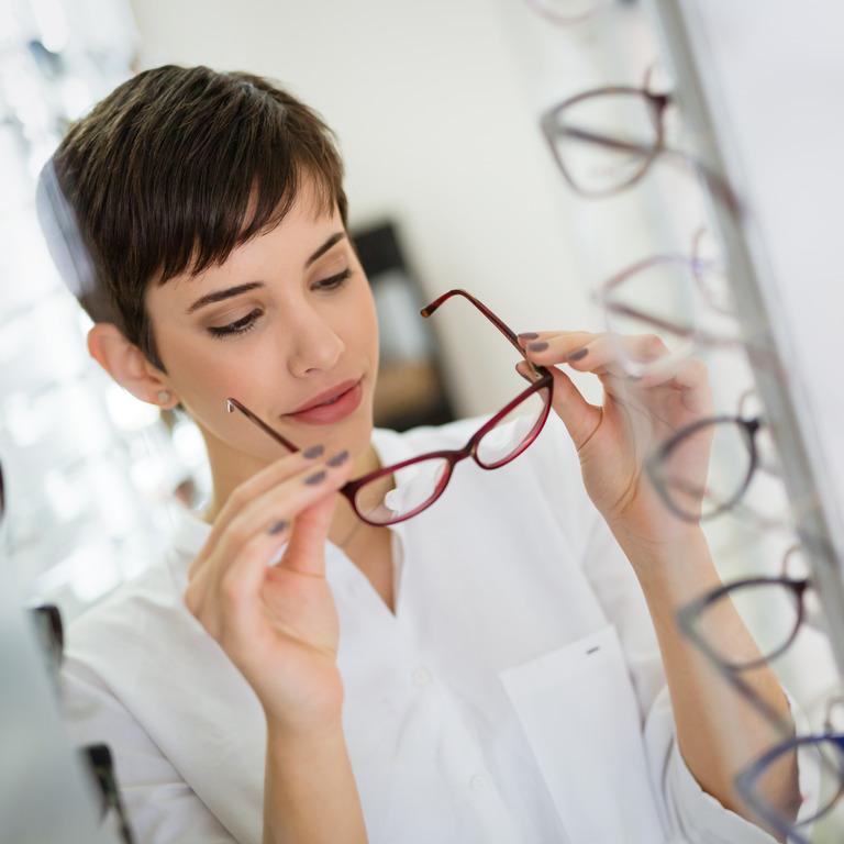 dunkelhaarige Frau probiert ein rotes Brillenmodell an