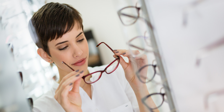 Frau probiert Brille in Brillenfachgeschäft.