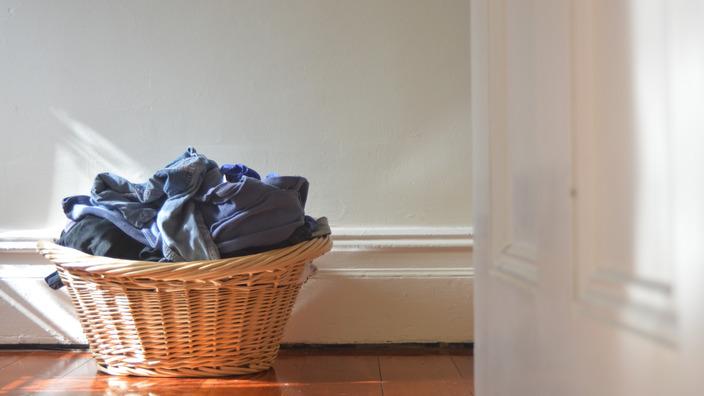 voller Wäschekorb steht vor einer Wand auf dem Boden