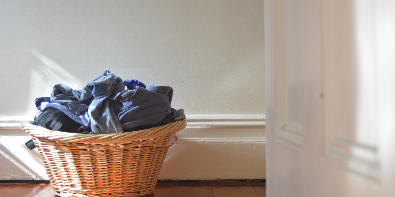 Korb mit Wäsche steht vor einer Wand auf dem Boden