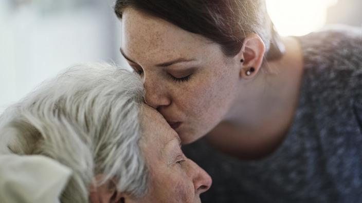 junge Frau küsst die Stirn einer alten Frau