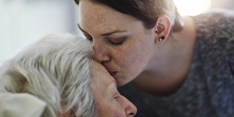 Tochter küsst ihre schwerkranke Mutter auf die Stirn